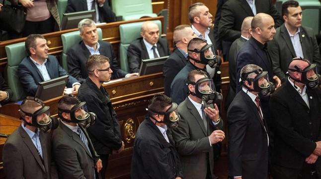 Policías kosovares con máscara entran en el Parlamento, tras el lanzamiento del cartucho con gas, este viernes.