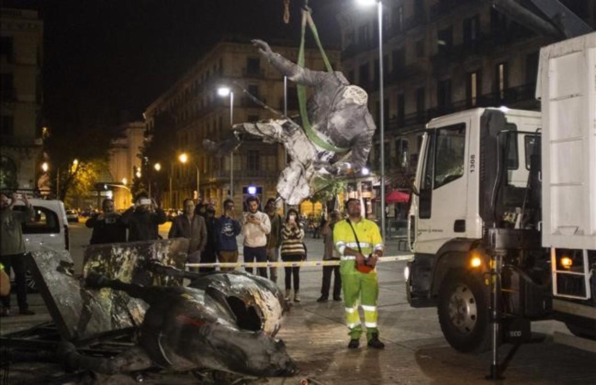 Unos operarios retiran la estatua rota de Franco, en la noche del jueves.