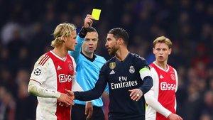 El árbitro le muestra la tarjeta amarilla a Sergio Ramos.
