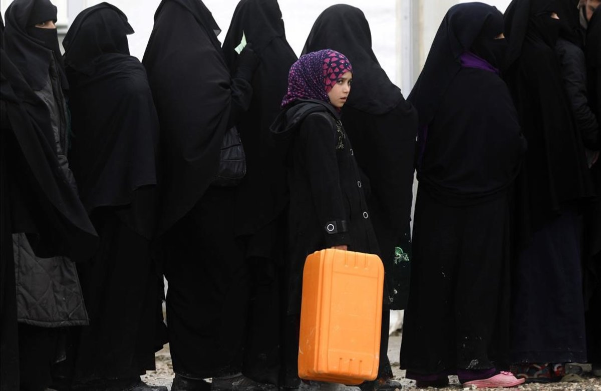 Una chica sostiene una maleta en una hilera de mujeres a la espera de recoger alimentos en el campo de refugiados de Al Hol, en el noreste de Siria
