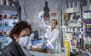 Una farmacéutica limpia la mampara de plástico de su comercio.