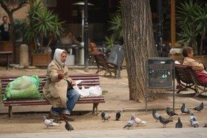 Una persona sin hogar dando de comer a las palomas.