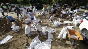 Vecinos de Baton Rouge colocan bolsas de arena para afianzar estructuras ant la inminente llegada de 'Barry'.
