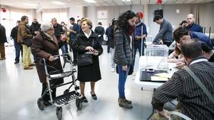 Vecinos de Vic guardan cola para votar en el Casal Mossèn Guiteras.