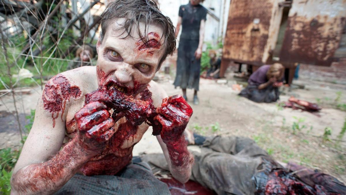 Uno de los zombis de la serie The walking dead, devorando a una de sus víctimas.