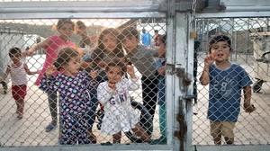 Niños tras la alambrada en un campo de refugiados de Grecia.