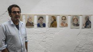 Àlex Raventós, con algunos de los retrataos de su exposición en la Retrateria.