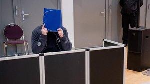 El enfermero Niels Högel se tapa la cara ante los medios.