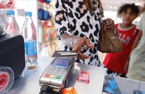 Una consumidora paga con tarjeta en una tienda de ropa.