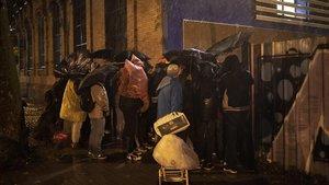 Unas veinte personas escuchan el recuento de los educadores sociales, frente a las puerta del recurso habilitado para la operación frío, la noche del miércoles.