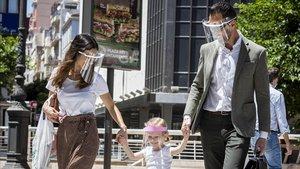 Una familia pasea por València protegida con mascarilla, este jueves.