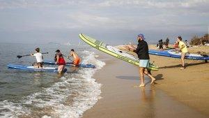 Miembros del Fithouse Training Center se disponen a salir a practicar paddle surf, en la playa de Ocata, El Masnou.