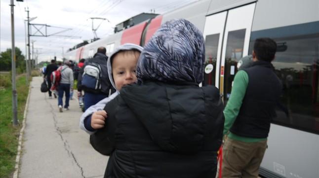 Una refugiado con su bebé a punto de subir al tren.