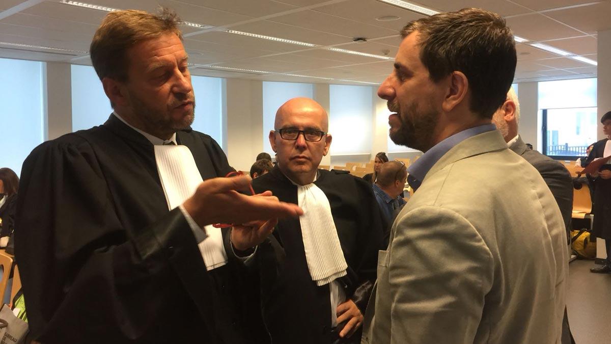 En la imagen, Toni Comín conversa con los letrados. El abogado de Llarena, Hakim Boularbah, explica en el vídeo que ha pedido que se posponga el caso hasta el próximo 25 de septiembre.