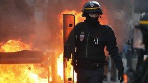 Un policía antidisturbios camina cerca del fuego de una barricada en Toulouse.