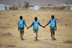 Niños refugiados, junto a un viejo autocar en Dundu (Angola).