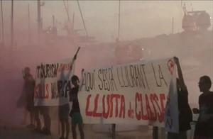 Captura del vídeo distribuido a través de las redes sociales por Arran de una acción contra el turismo con pancartas y bengalasen el puerto deportivo de Palma de Mallorca.