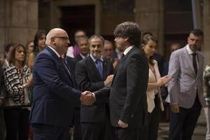 Carles Puigdemont da la mano al destituido 'conseller' Jordi Baiget, ayer.