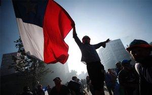 Una personas porta la bandera de Chile en medio de las protestas sociales.