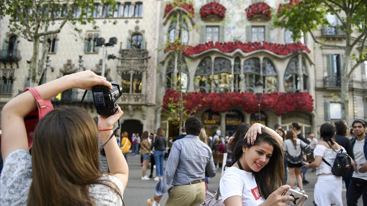 Decenas de flores decoran la fachada de la Casa Batlló horas antes de la diada de Sant Jordi.