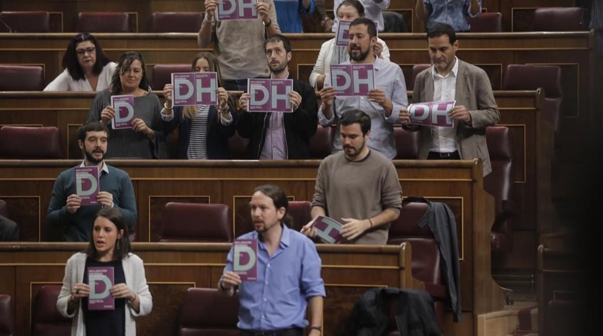 Diputados de Podemos muestran carteles a favor de los derechos humanos al inicio del pleno del Congreso.