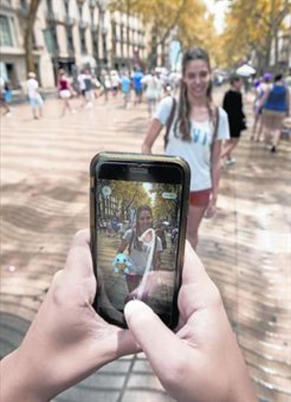 Dos jóvenes utilizan la aplicación Pokémon Go en la Rambla.