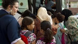 Unos padres despiden a sus hijos ante el autocar que les lleva a una excursión escolar.