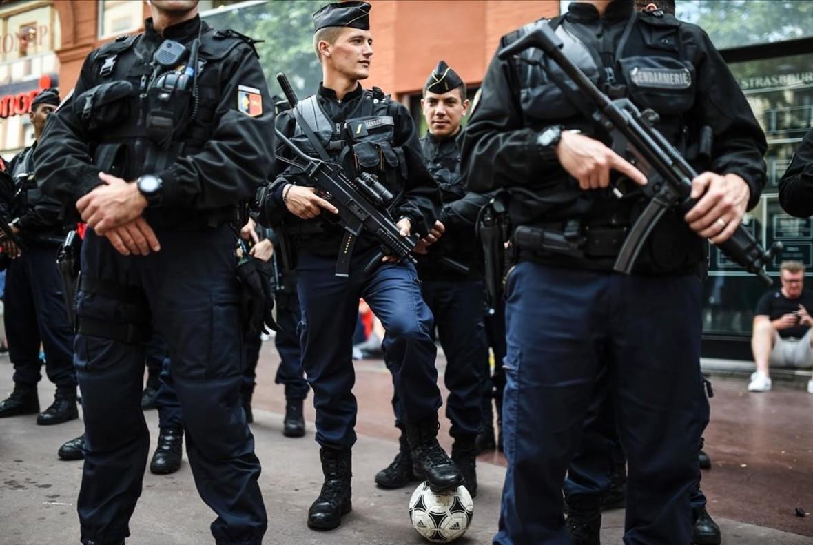 Un gendarme francés controla un balón de los aficionadosde Gales minentras patrullan por las calles de Toulouse.