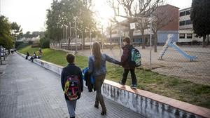 Una madre recoge a sus dos hijos, alumnosde la escuela Elisa Badia, enBarberàdel Vallès.