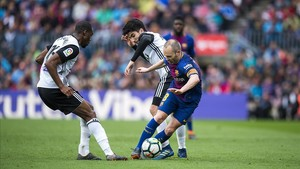 Iniesta se marcha de Kondogbia y Soler en el Barça-Valencia del Camp Nou.