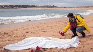Una mujer coloca flores junto al cadáver de un migrante que falleció cuando iba a bordo de una patera en la costa de Canos de Meca, en Cádiz, en noviembre.
