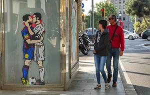 Una pareja pasa junto a El amor es ciego, título de la obra de Tvboy.