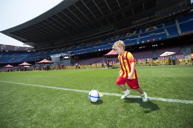 Un joven seguidor culé corretea con el balón por el césped del Camp Nou.