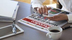 Una lectora consula el diario en móvil y papel.