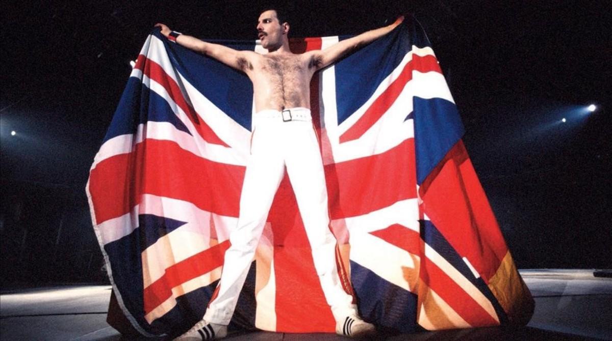 Freddie Mercury sostiene la bandera de Reino Unido durante un concierto con su grupo, Queen.