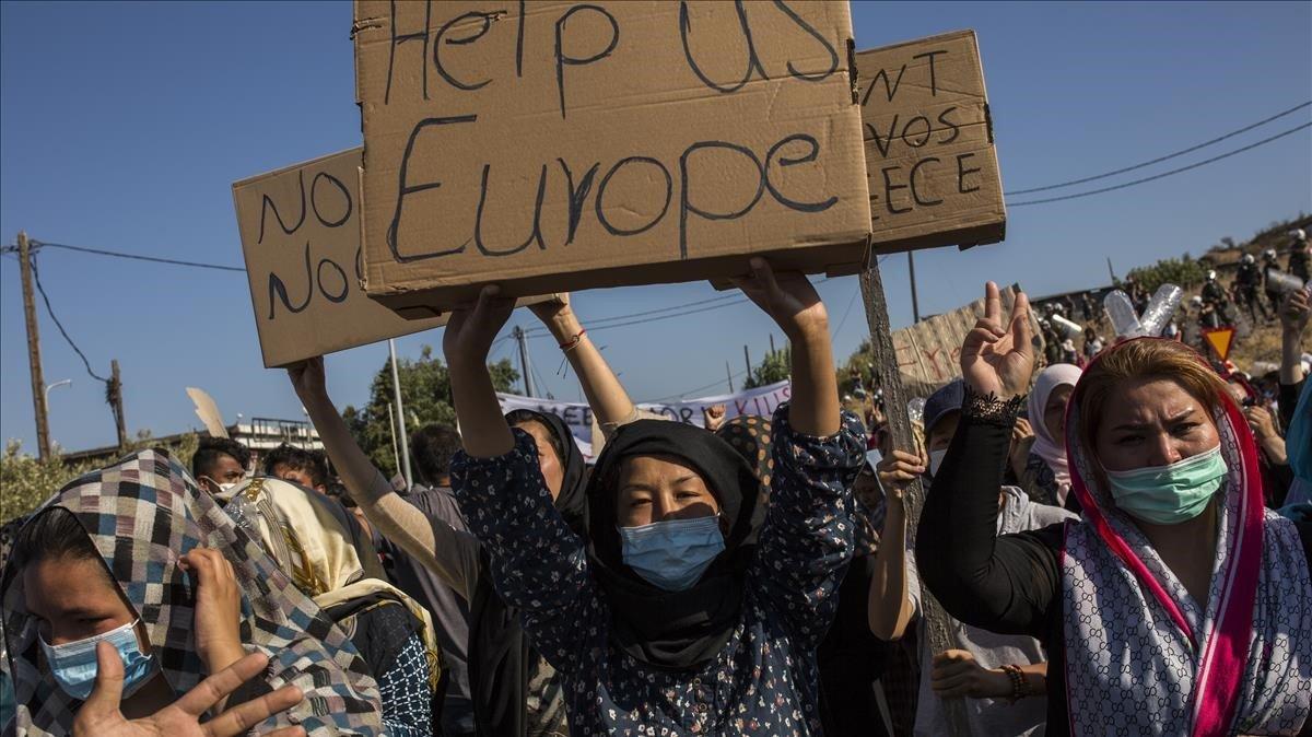 Una mujer refugiada de Moria muestra en una protesta un cartón en el que hay escrito en inglés Europa ayúdanos.