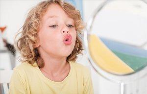 Un niño habla solo frente al espejo.
