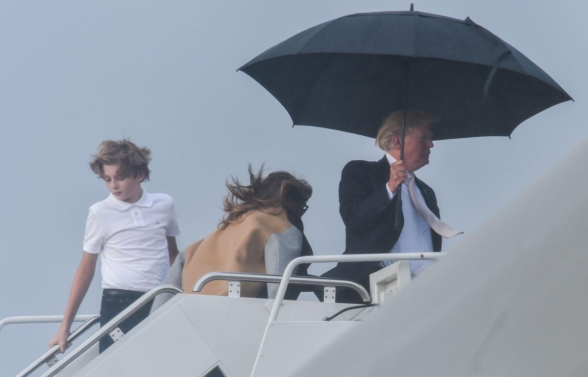 El presidente de EEUU, Donald Trump, sostiene un amplio paraguas para protegerse de la lluvia, mientras espera a su mujer Melania y a su hijo Barron, durante el embarque del Air Force One en Flordia.