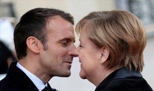 El presidente francés, Emmanuel Macron, y la cancillera alemana, Angela Merkel, se saludan en el Palacio del Elíseo, en París, durante la conmemoración del centenario del Armisticio.
