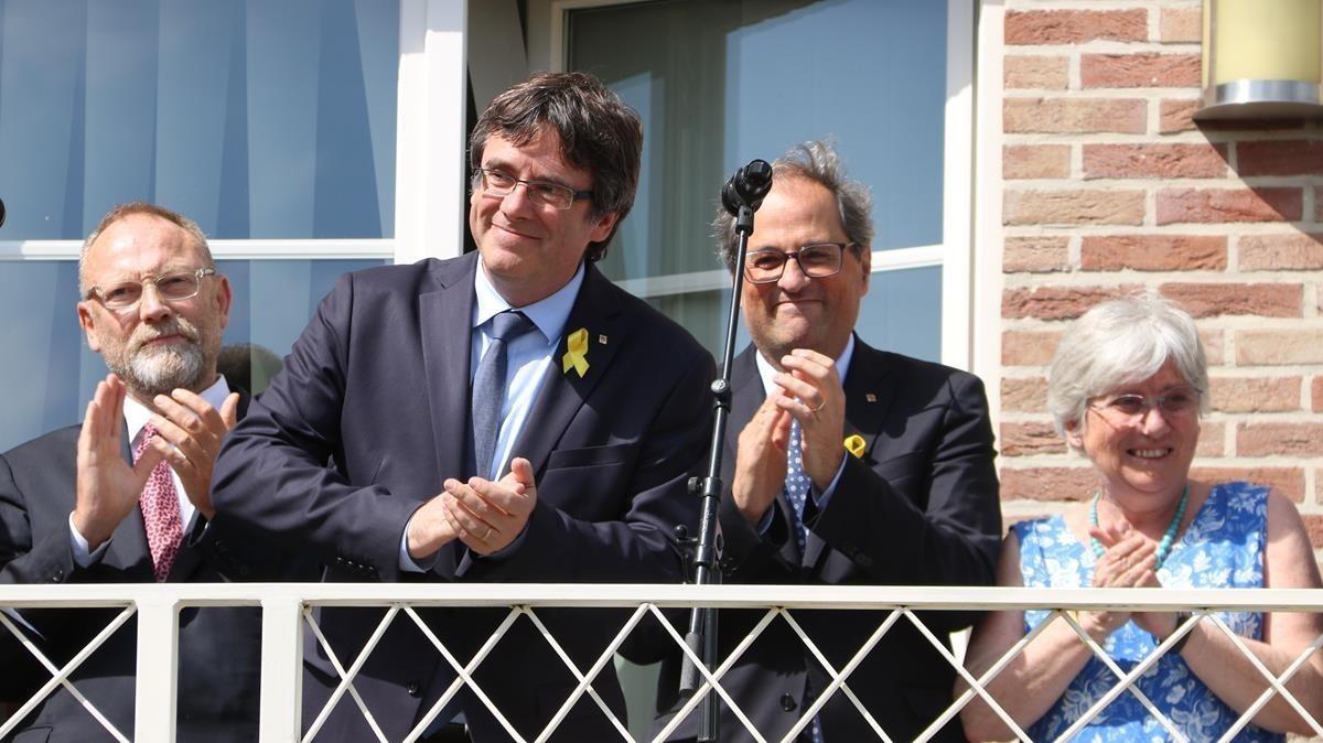 Carles Puigdemont, junto a Quim Torra y Clara Ponsatí, en el balcón de la casa de Waterloo el 28 de julio.