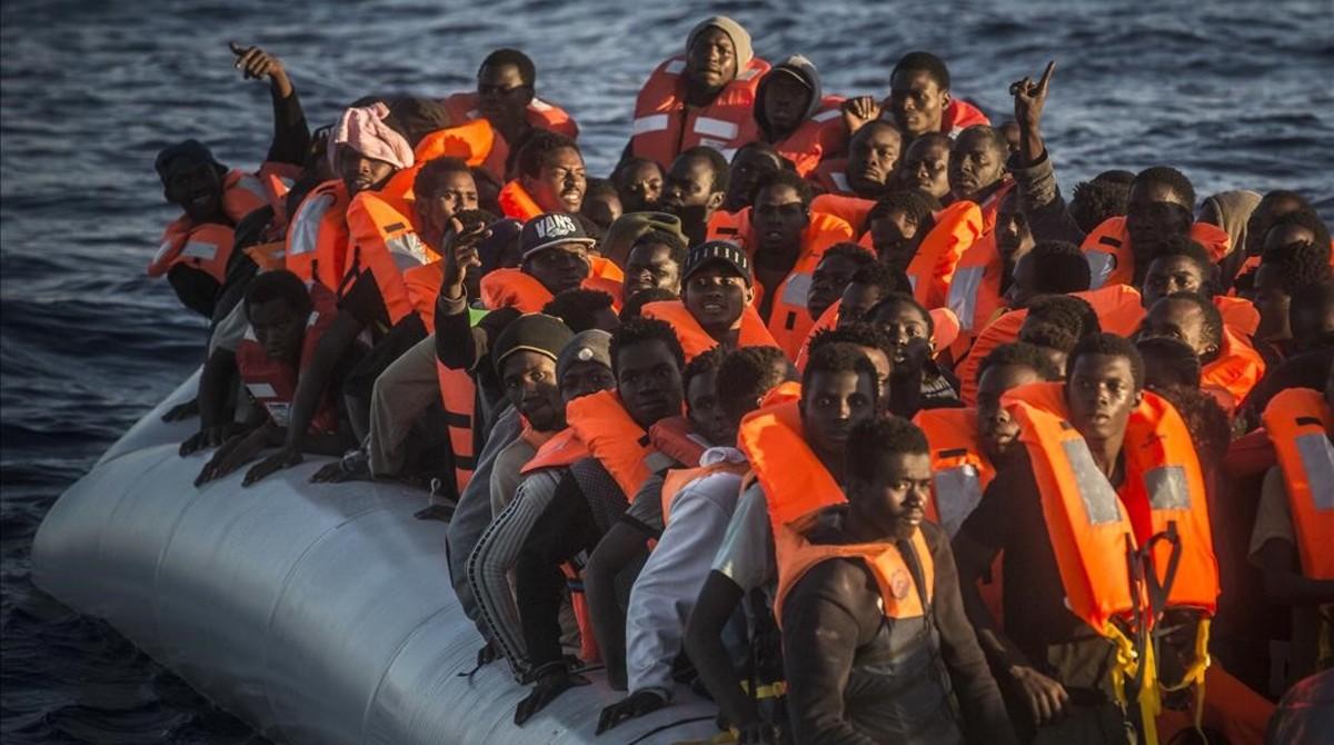 Refugiados e inmigrantes subsaharianos esperan en una barca neumática atiborrada a ser rescatados por el 'Astral', el 19 de julio, a 24 millas al norte de Sabratha (Libia).