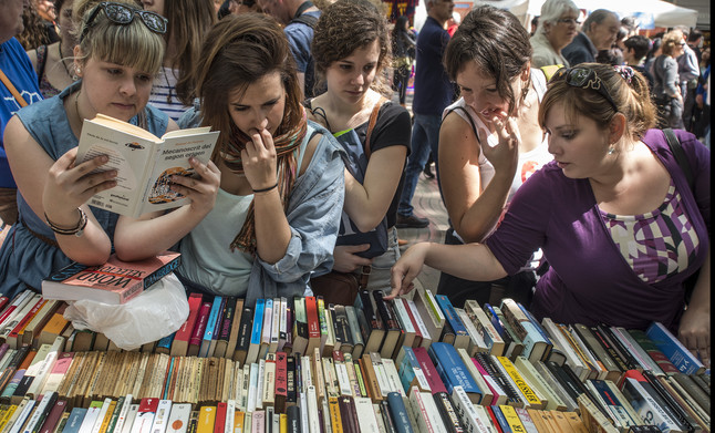 Un grupo de mujeres consulta varios libros en una parada de Barcelona.
