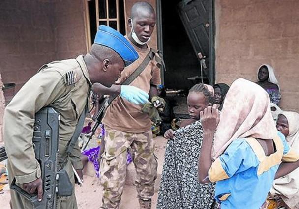 Un soldado nigeriano junto a algunas de las chicas rescatadas de las manos de Boko Haram.