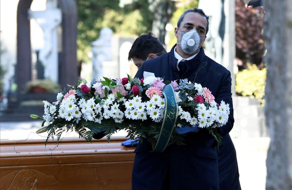 Trabajadores de un cementerio trasladan un féretro, en el cementerio de Bérgamo, Italia.