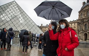 Turistas con mascarillas para protegerse del coronavirus, frente al Louvre de París.