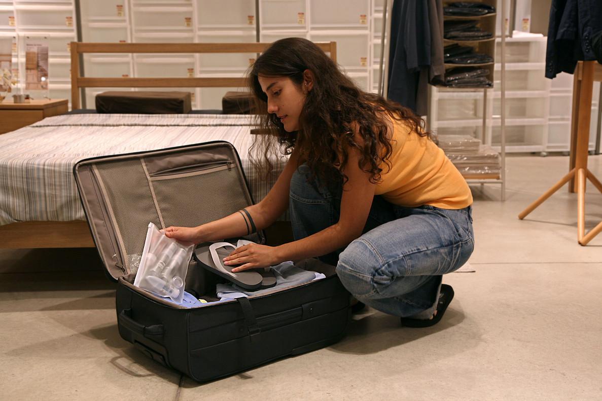 e925edc04 Una joven prepara su equipaje de mano para un viaje en avión.