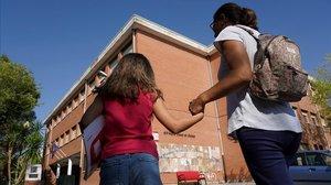 Una madre acompaña a su hija al colegio para recoger los libros de texto, el pasado martes en Madrid.