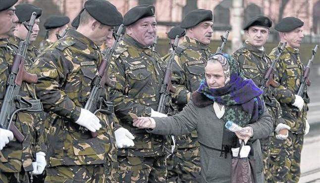 Una mujer ofrece galletas a los soldados de guardia rumanos que participan en los actos conmemorativos de la revolución, esta semana en Bucarest.