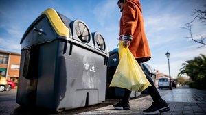 Una mujer recicla envases de plástico en el contenedor amarillo.