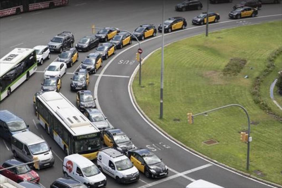 Varios taxis circulan a marcha lenta por la plaza de Espanya.